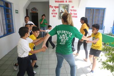 Une volontaire joue avec des enfants lors de sa mission humanitaire à l'étranger