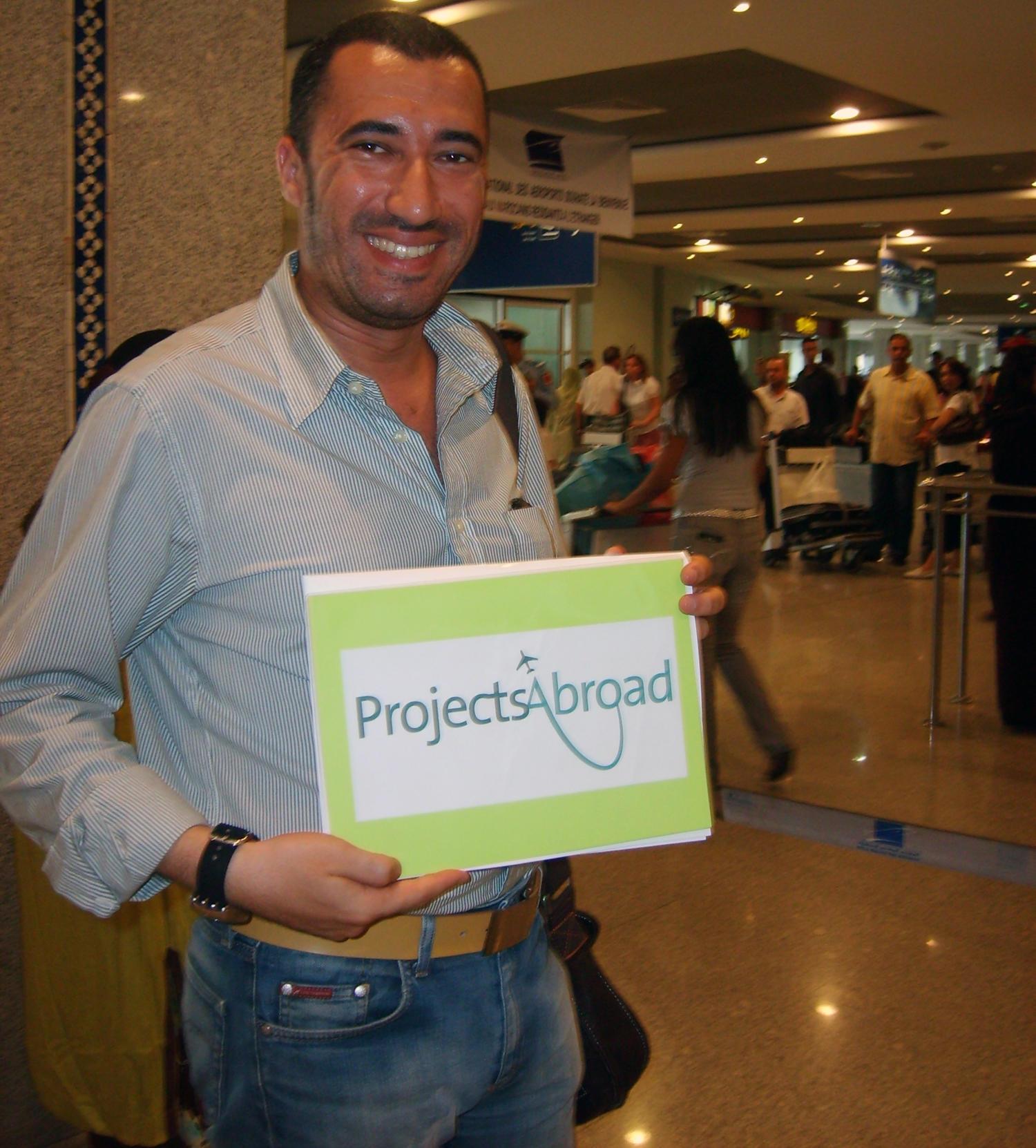 Un membre de l'équipe locale tient une pancarte Projects Abroad à l'aéroport au Maroc