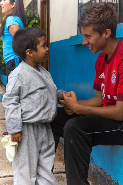 Un volontaire discute avec un enfant lors de sa mission de volontariat en encadrement sportif sur un programme d'été au Belize