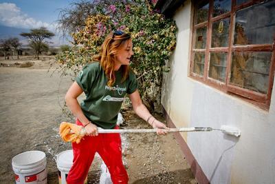 Une volontaire peint le mur d'une école sur le chantier construction en Tanzanie