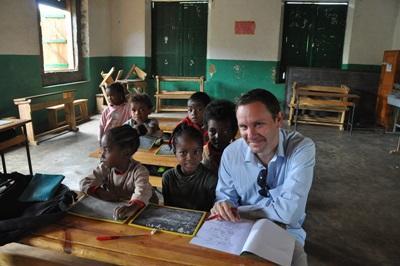 Un volontaire assis à une table de classe apprend le malgache avec des enfants