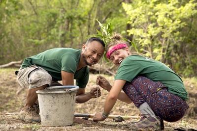 Une volontaire plante un arbre, aidée d`un membre du staff local