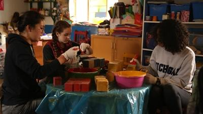 Des jeunes volontaires repeignent des jouets en bois lors de leur mission humanitaire et communautaire au Pérou