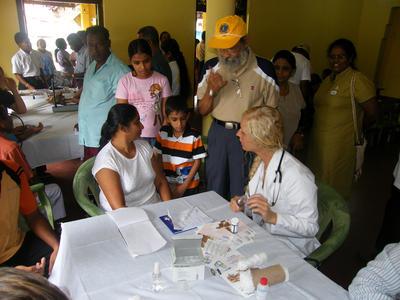 Une volontaire échange avec des patiens lors de sa mission en pharmacie à l'étranger