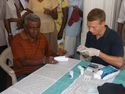 Une volontaire soigne un habitant de quartiers défavorisés