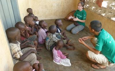 Deux volontaires parlent avec des enfants dans un centre d'accueil lors d'une mission en santé publique à Lomé au Togo.