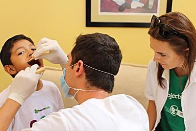 Un enfant reçoit un check-up dentaire d'un volontaire au Mexique.