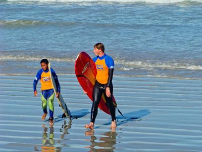 Un volontaire sort de l'eau avec un jeune après une session surf en Afrique du Sud
