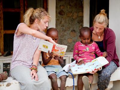 Deux volontaires en mission humanitaire d'aide à l'enfance en Tanzanie lisent avec des enfants