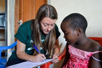 Une volontaire assise avec une jeune fille collecte des données lors de son projet en Tanzanie